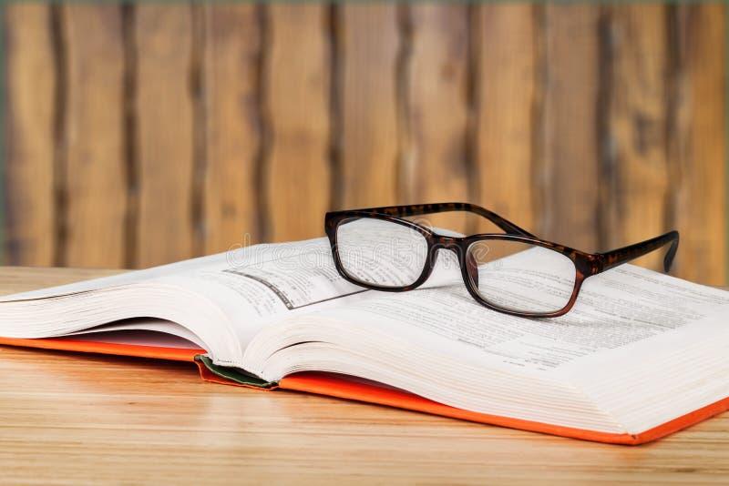 Öppna boken och exponeringsglas på trätabellen royaltyfria foton
