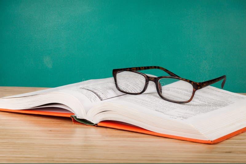 Öppna boken och exponeringsglas på trätabellen royaltyfri bild