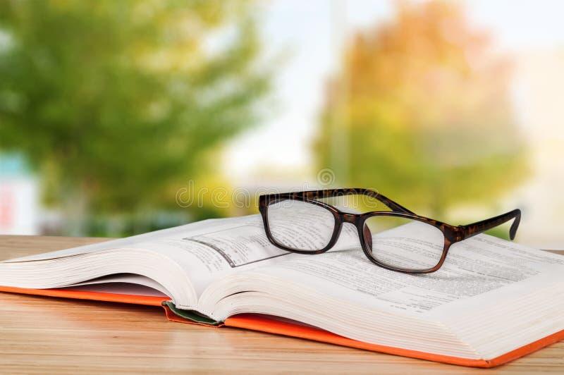 Öppna boken och exponeringsglas på trätabellen arkivfoto