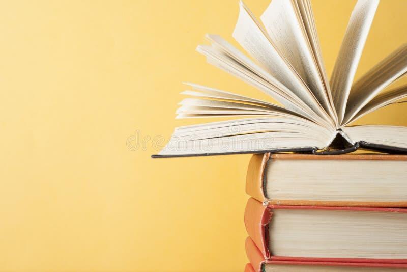 Öppna boken på bunt av böcker på trätabellen sax och blyertspennor på bakgrunden av kraft papper tillbaka skola till Utrymme för  arkivfoto