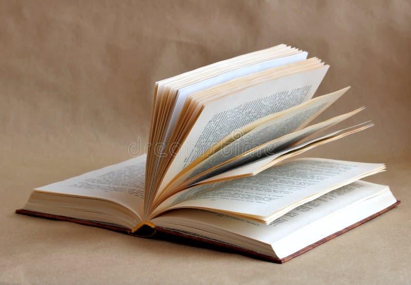 öppna boken på en beige bakgrund royaltyfria bilder