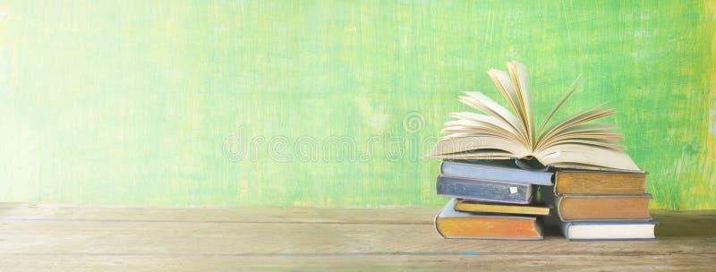 Öppna boken på en bunt av böcker, royaltyfri bild