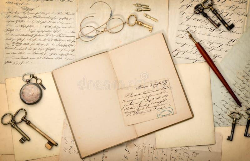Öppna boken, tappningtillbehör, gamla bokstäver Pappers- bac för nostalgiker arkivbild