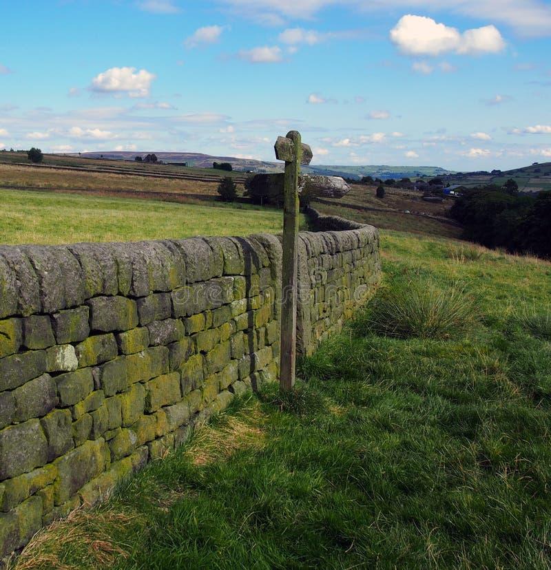 Öppna bygd med riktningstecknet bredvid en vägg för torr sten royaltyfri bild