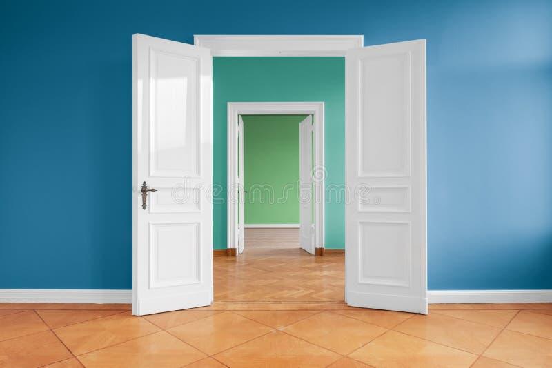 Öppna dörrar i tom lägenhet med kulöra väggar arkivfoto