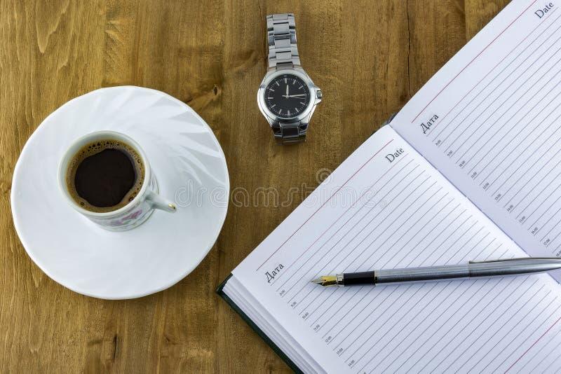 Öppna dagstidningen, en klocka med ett armband och en kopp kaffe på en uppvakta arkivfoto