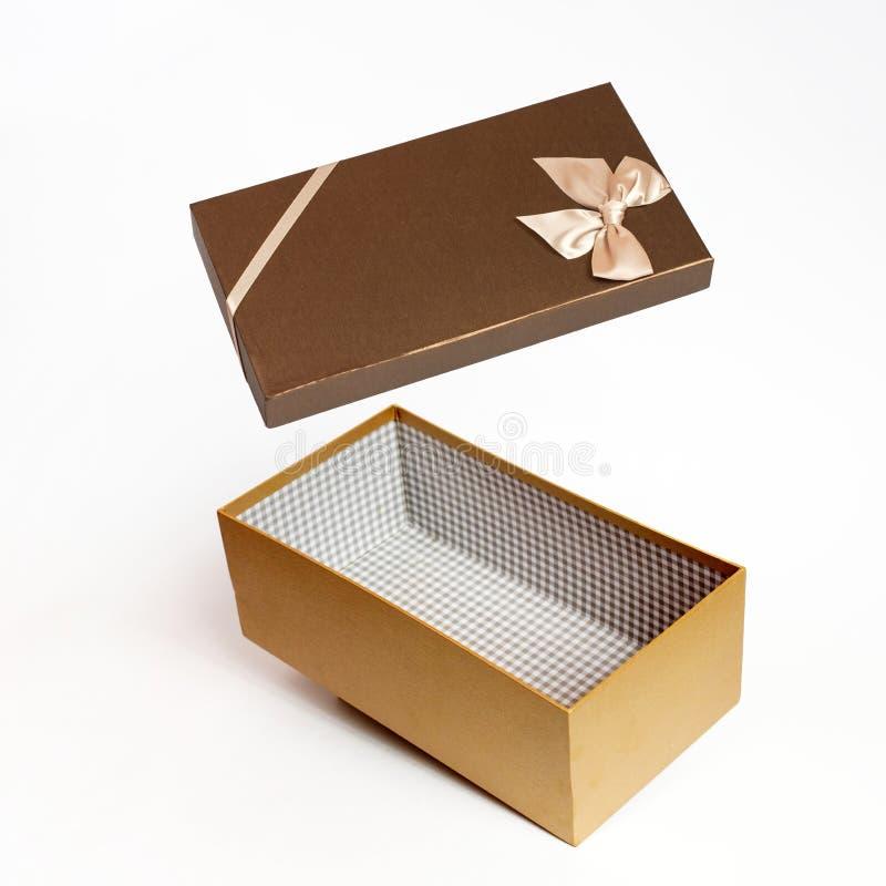 Öppna den bruna gåvaasken på vit bakgrund arkivfoto