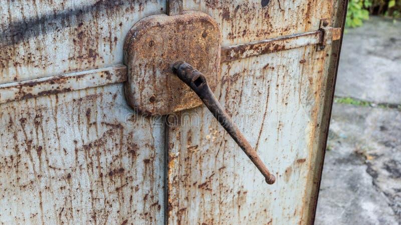 Öppna den gamla rostiga metalldörren med spaken royaltyfria foton