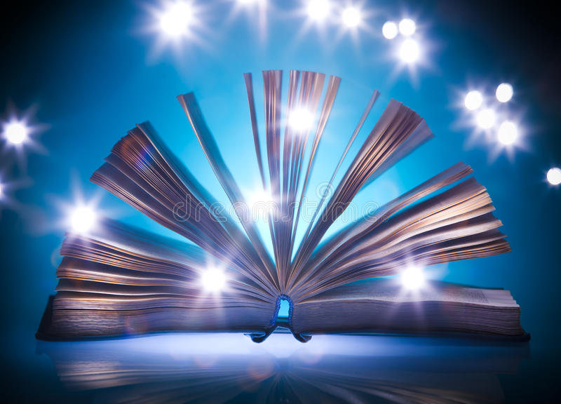 Öppna den gammala boken, mystisk blå lampa på bakgrund arkivbilder