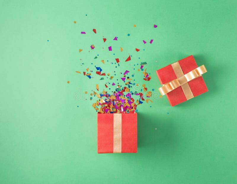 Öppna den röda gåvaasken med konfettier för det olika partiet royaltyfria bilder