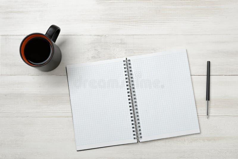 Öppna den tomma anteckningsboken och svärta pennan på den med koppen av varmt kaffe arkivbild