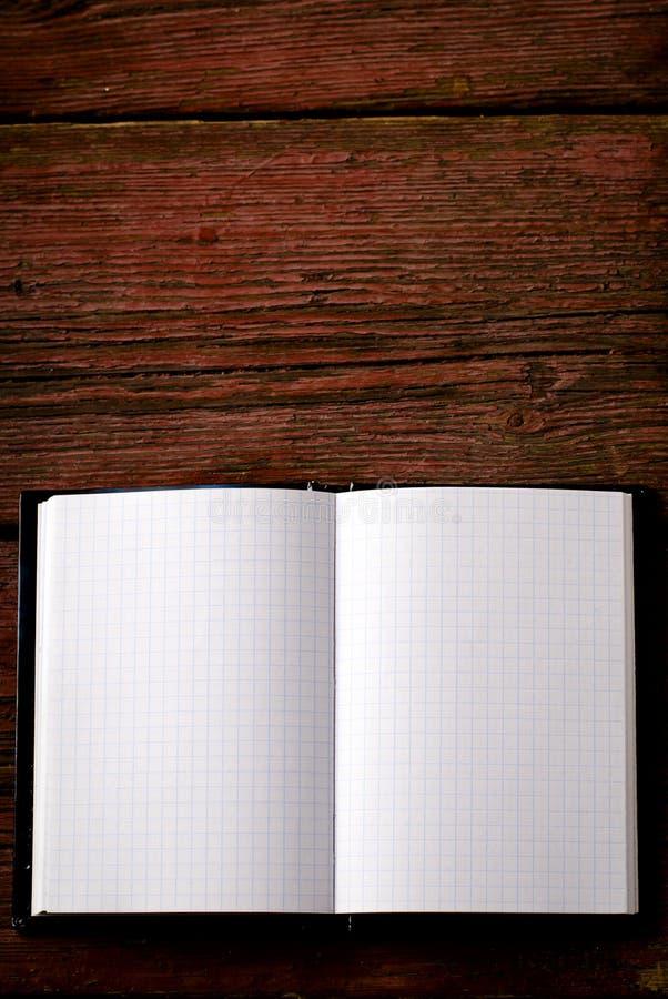 Öppna den tomma notepaden på den gamla trätabellen arkivbild