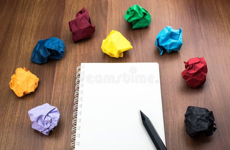 Öppna den tomma vita boken och blyertspennan med den skrynkliga gruppen av färgrikt arkivfoto