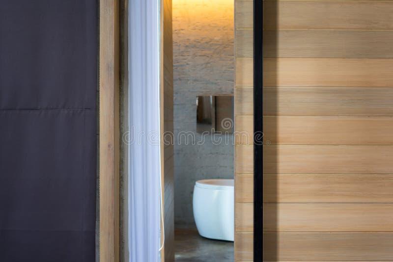 Öppna den träglidande badrumdörren med det vita badkaret och gardiner royaltyfria bilder