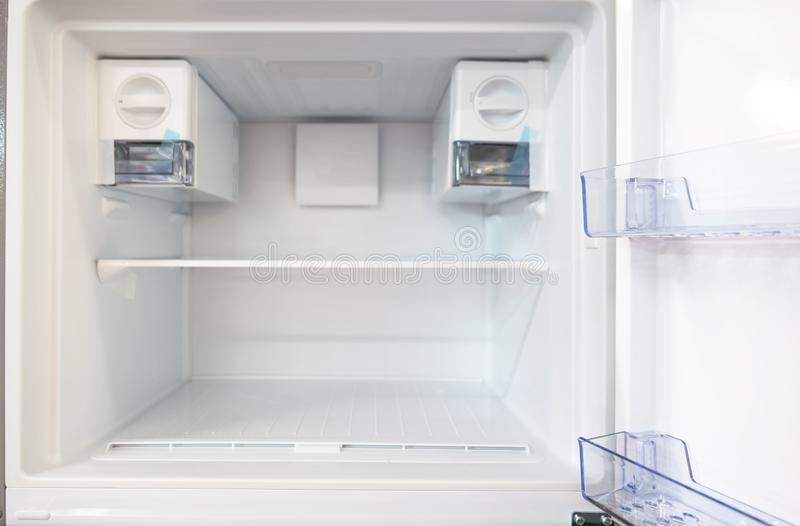 Öppna det tomma nya vita kylskåpet inom kylen med hyllor royaltyfria bilder