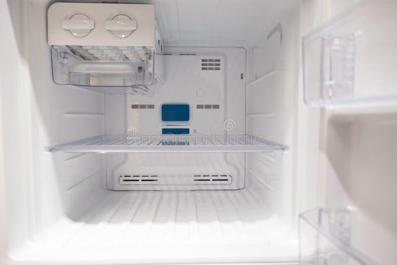 Öppna det tomma nya vita kylskåpet inom kylen med hyllor royaltyfria foton