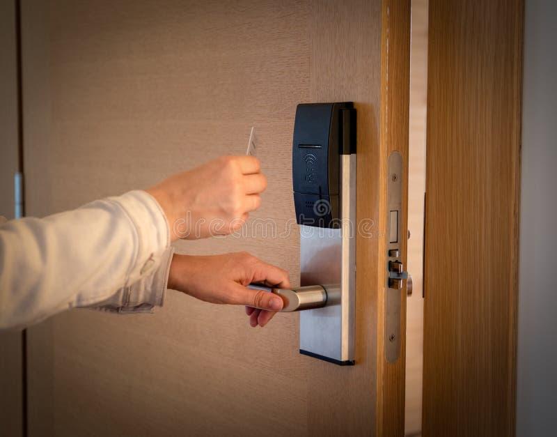 Öppna en hotelldörr med det keyless tillträdeskortet arkivfoton