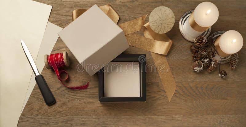 Öppna en vit julklapp som väntar på att packas över ett träbord royaltyfri fotografi