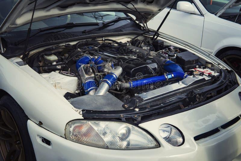 Öppna huven av en bil med sikten av motorn E Motorn knackar Buse för motorkörningar En bil önskar en reparation Medelunsh arkivfoton