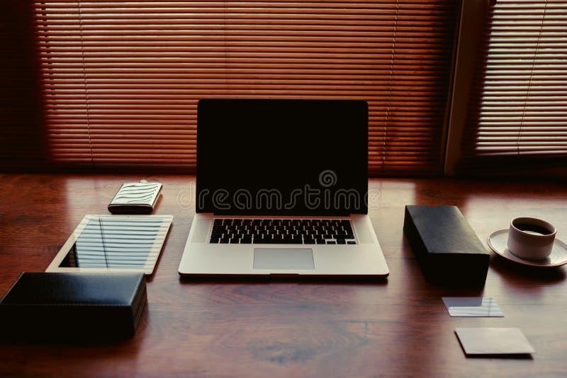 Öppna kontoret för det textural bruna skrivbordet för bärbara datorn och för minnestavlan det moderna bredvid en kopp av svart ka royaltyfri foto