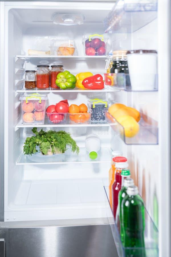 Öppna kylen med nya frukt och grönsaker arkivbilder