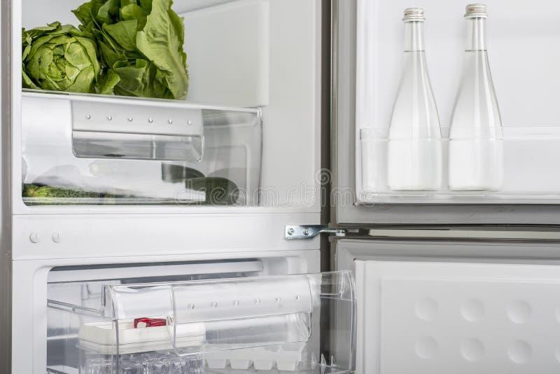 Öppna kylen mycket av nya frukter och grönsaker arkivbild