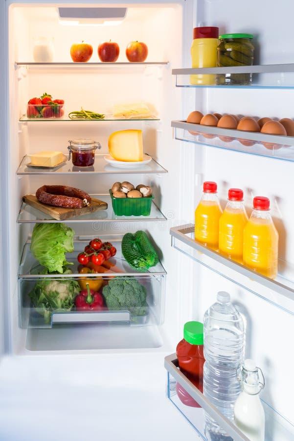 Öppna kylen som fylls med mat royaltyfri foto