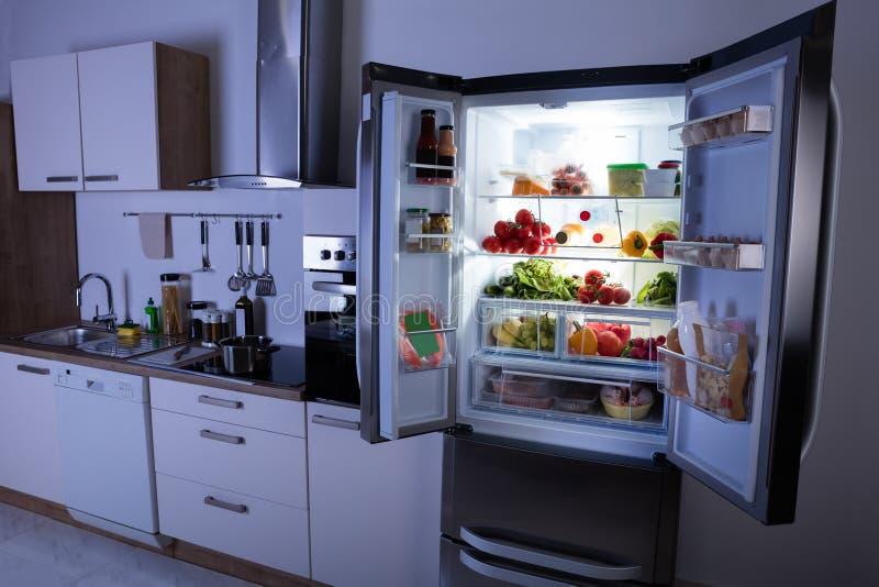 Öppna kylskåpet i modernt kök arkivbilder