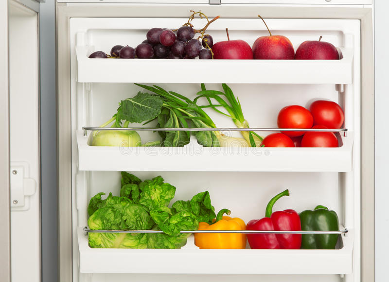 Öppna kylskåpet mycket av nya frukt och grönsaker royaltyfri foto