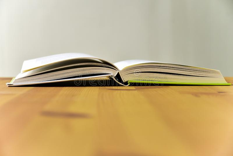 Öppna läsbok, liggande på träbordet arkivbilder