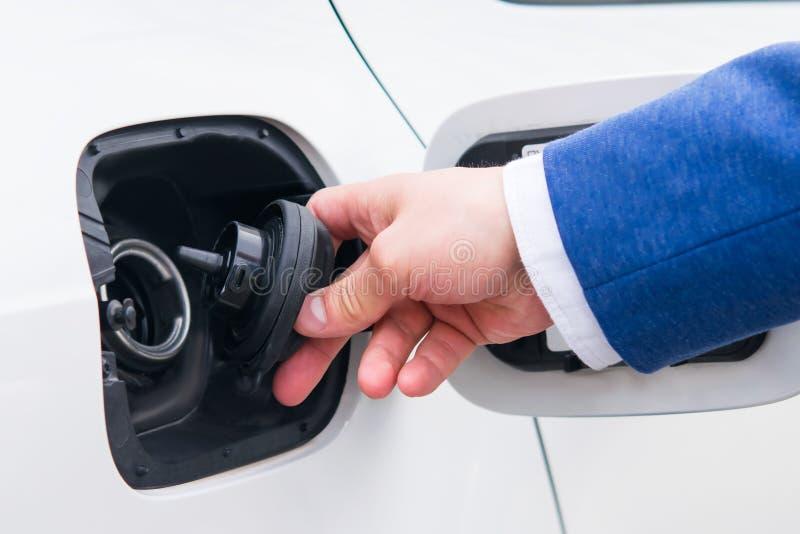 Öppna locket av bränslebehållaren i bilen Medel som tankar på en bensinstationaffärsman i en dräkt royaltyfri foto