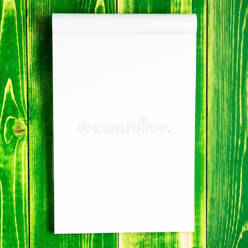 Öppna notepaden för tecken och skissar på ett ljust - grön träbakgrund arkivbild