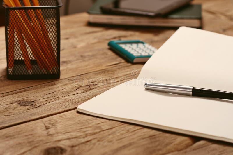 Öppna notepaden med pennan och räknemaskinen på skrivbordet fotografering för bildbyråer