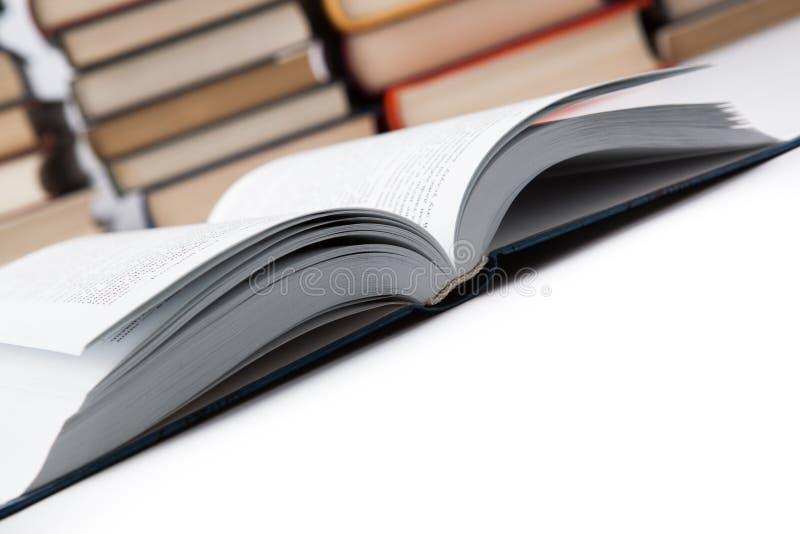 Öppna på boken med högen av böcker fotografering för bildbyråer