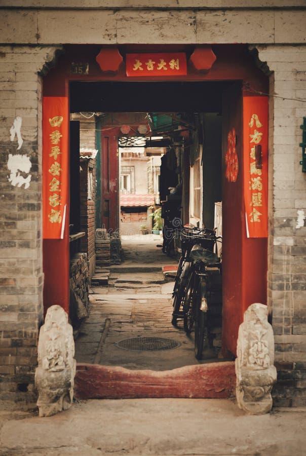 Öppna portar till Hutong Ett tecken på båda sidor av ingången läser 'välkomnande 'såväl som en önska för lycka och bra lycka hemm royaltyfri bild