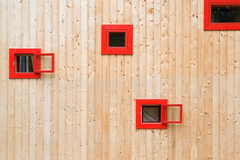 Öppna röda fönster på en trävägg arkivfoto