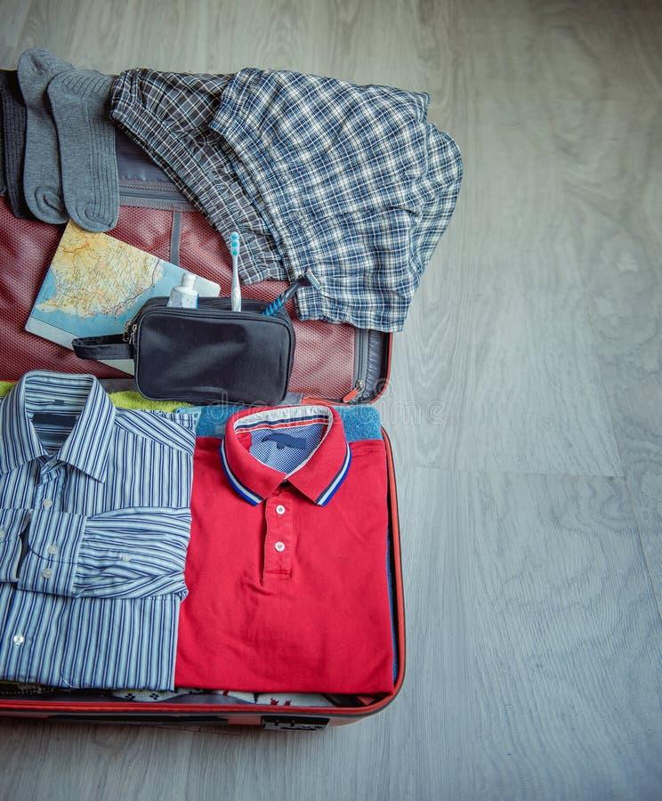Öppna resväskan med kläder på trägolv fotografering för bildbyråer