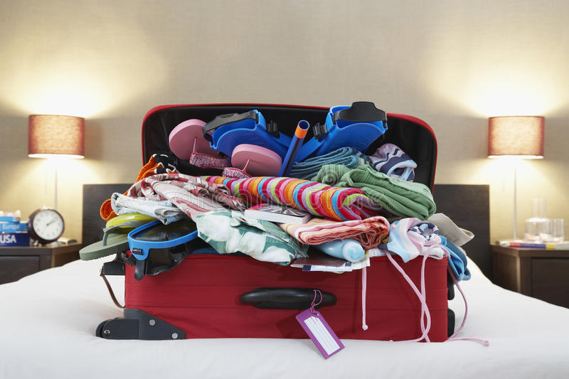Öppna resväskan på säng royaltyfri fotografi