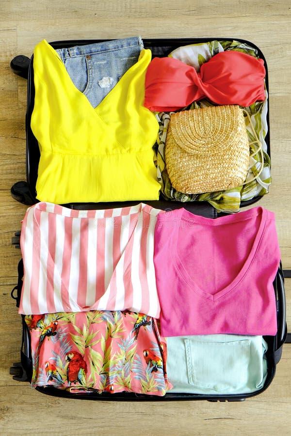Öppna resväskan som packas fullständigt med vikt kläder och tillbehör för kvinna` s på golvet Kvinnaemballage för tropiskt semest royaltyfria foton