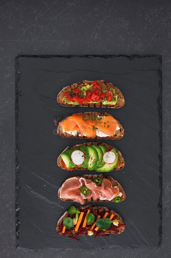 Öppna smörgåsar för rågbröd med olika toppningar arkivbild