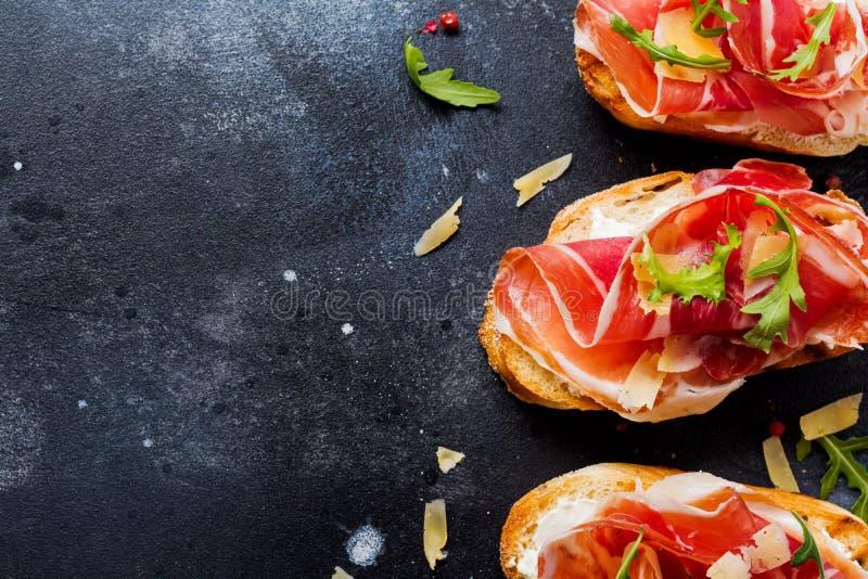 Öppna smörgåsar med jamon, arugula och hårdost på en konkret gammal mörk bakgrund fotografering för bildbyråer