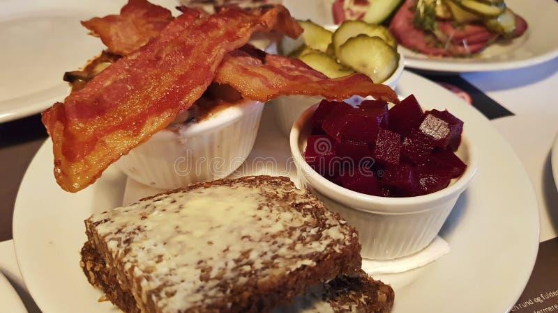 Öppna smörgåsen panera smör Gravade beta som tärnas Bacon som stekas till guld- brunt arkivbild
