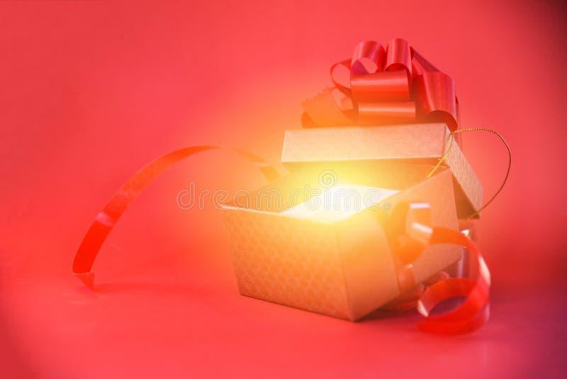 Öppna strålar för gåvaask tänder på den röda närvarande asken för röd bakgrund med den röda bandpilbågen för år för ferie för gla royaltyfria foton