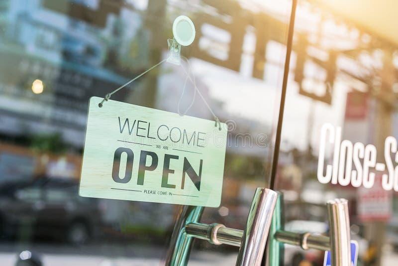 Öppna tecknet som är brett till och med exponeringsglaset av fönstret på coffee shop arkivfoto