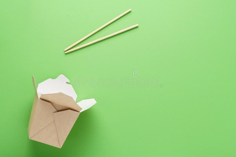 Öppna tomma kraft pappersask och pinnar på grön bakgrund royaltyfria bilder