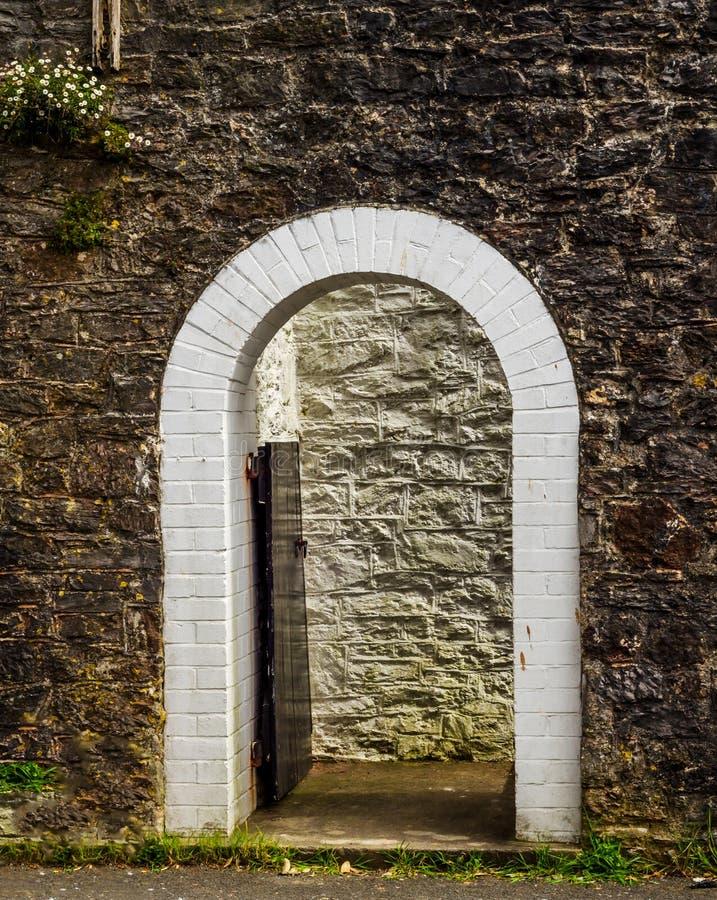 Öppna trädörren med den spetsiga gotiska bågen på en vit stenvägg fotografering för bildbyråer