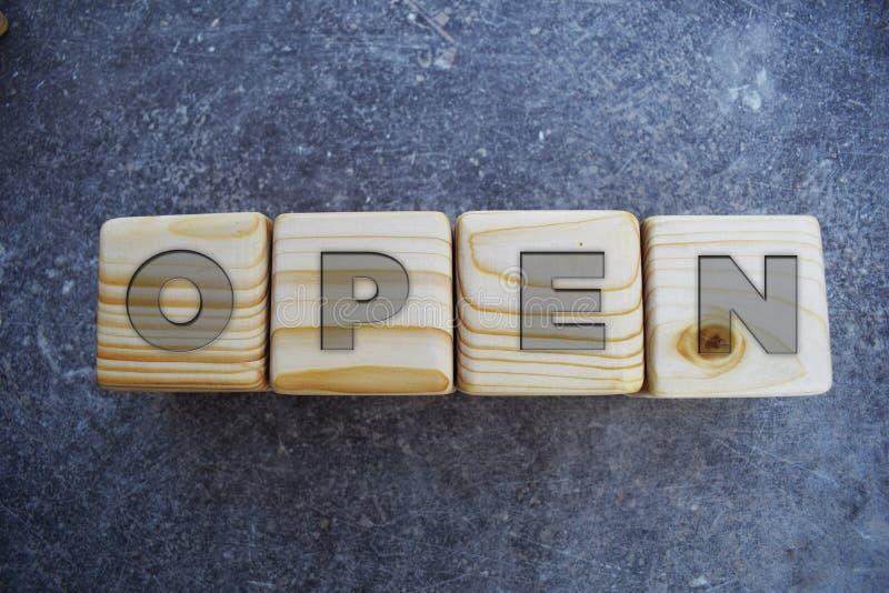 Öppna - träkvarterbrev på grå bakgrund royaltyfri foto