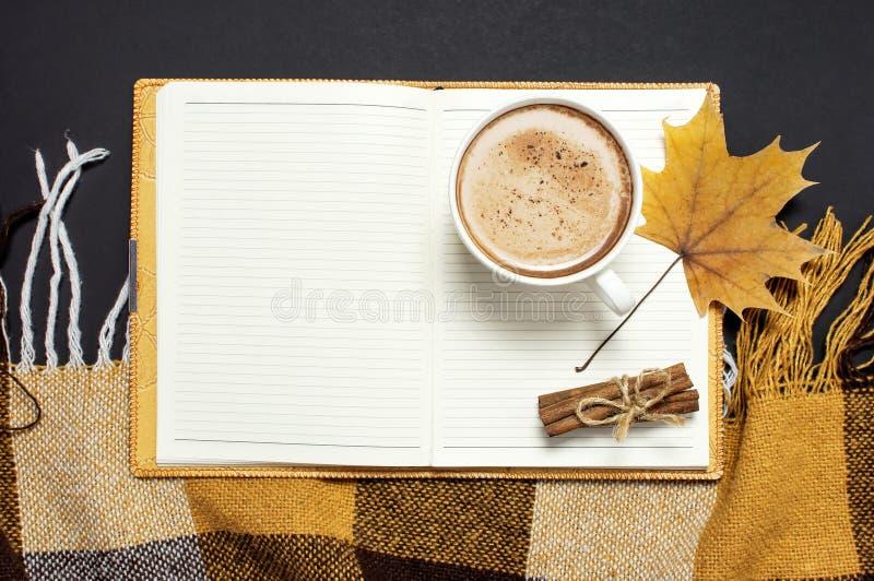 Öppnad anteckningsbok, kopp av pumpakakao eller kaffe, kanelbrun gul höstlönnlöv, orange brun rutig pläd på svart backgro fotografering för bildbyråer