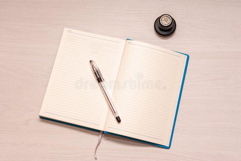 Öppnad anteckningsbok med den svarta pennan och den officiella stämpeln på en vit trätabell, bästa sikt royaltyfria foton