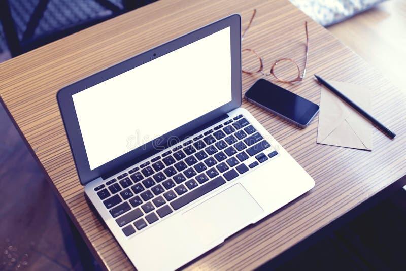 Öppnad bärbar datordator med utrymme för tom skärm för designorienteringen, mobiltelefon, exponeringsglas, kuvert Kafé- eller Co- royaltyfri bild